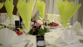 Feestelijke die lijst met glazen en bloemenboeket wordt geplaatst stock videobeelden