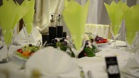 Feestelijke die lijst met glazen en bloemenboeket wordt geplaatst stock footage
