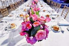 Feestelijke dinerlijst met mooie bloemenboeketten Stock Afbeeldingen