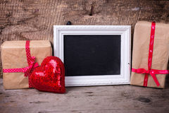 Feestelijke giftdoos, decoratief rood hart en leeg bord Stock Fotografie