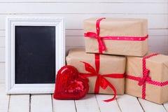 Feestelijke giftdozen, decoratief hart en leeg bord Stock Fotografie
