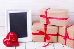 Feestelijke giftdozen, decoratief hart en leeg bord op wh Stock Afbeeldingen