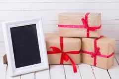 Feestelijke giftdozen en leeg bord op witte houten backgro Stock Foto