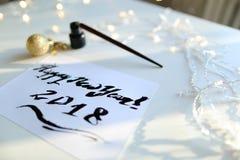 Feestelijke groetkaart met nieuw die jaar met zwarte inkt op papier wordt gemaakt Stock Foto