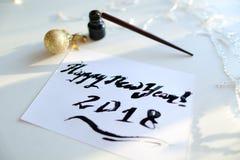 Feestelijke groetkaart met nieuw die jaar met zwarte inkt op papier wordt gemaakt stock afbeelding