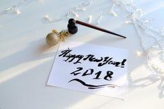 Feestelijke groetkaart met nieuw die jaar met zwarte inkt op papier wordt gemaakt Royalty-vrije Stock Foto's