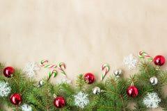 Feestelijke Kerstmisgrens met rode en zilveren ballen op spartakken en sneeuwvlokken op rustieke beige achtergrond Stock Afbeeldingen