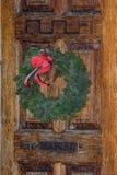 Feestelijke Kerstmiskroon op deur bij Kersttijd Royalty-vrije Stock Afbeeldingen