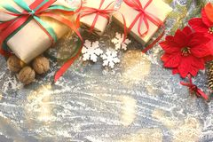 Feestelijke Kerstmissamenstelling met giften, dozen, kegels, okkernoten, rode bloemen van poinsettia op een houten achtergrond me stock fotografie