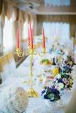 Feestelijke lijst die met bloemen en kaarsen wordt verfraaid Stock Foto