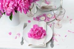 Feestelijke lijst die met roze pioenen plaatsen Stock Afbeeldingen