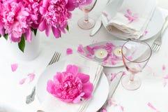 Feestelijke lijst die met roze pioenen plaatsen Stock Foto