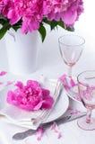 Feestelijke lijst die met roze pioenen plaatsen Royalty-vrije Stock Afbeeldingen