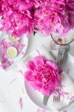 Feestelijke lijst die met roze pioenen plaatsen Royalty-vrije Stock Foto's