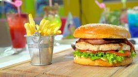Feestelijke lunch met hamburger, frieten en sommige gekleurde cocktails stock video