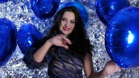 Feestelijke stemming, gelukkig wijfje met opblaasbare die ballons in handen dichtbij muur met folie wordt verfraaid stock videobeelden