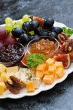 Feestelijke voorgerechten - kazen, vruchten en jam, verticale close-up Royalty-vrije Stock Foto