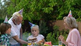 Feestvarken het blazen uit schouwt het maken van wens, gelukkige kinderjaren met grootouders stock videobeelden