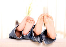 Feet. Child foot with jeans over white background Stock Photos