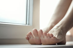 Feet. Of the woman sitting on windowsill. Close-up horizontal photo with shallow depth of field for natural view Stock Photo