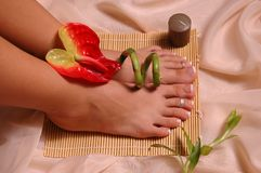 Feet. Pedicured feet, tropical flower, bamboo plant on silk cloth Royalty Free Stock Images