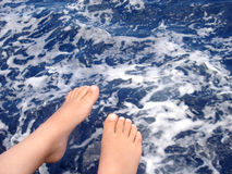 Feet. Boy sitting on a boat with his feet above the ocean Stock Image