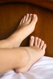 Feet. Young girls perfect feet in bed Stock Photography