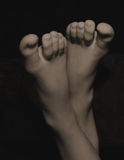 Feet. A pair of youth feet in sepia toning on black background Royalty Free Stock Image