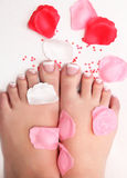 Feet. Designed nails on the foot with petals of roses Stock Images