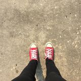 Feet From Above Concept, Teenage Person in Red Sneakers Standing on Background Royalty Free Stock Photography
