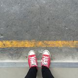 Feet From Above Concept, Teenage Person in Red Sneakers Standing on Background Royalty Free Stock Image