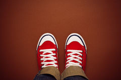 Feet From Above, Teenager in Sneakers Standing on Brown Backgrou Royalty Free Stock Photos