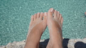 Feet above turquoise water. Feet with sand above turquoise and crystal clear water Royalty Free Stock Images