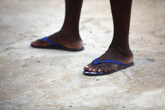 Feet of an African man in blue flip flops. On a stony background stock photos