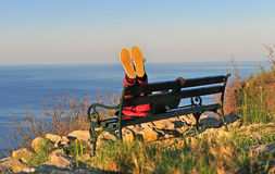 Feet in the air, man lying on the bench Royalty Free Stock Image