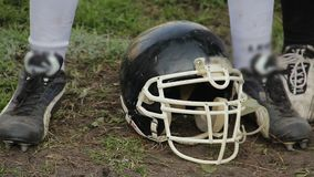 Feet of american football player anxious to start game, helmet lying on ground stock footage