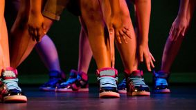 Feet, ankles and arms of hip-hop performers. In colorful sneakers Stock Image