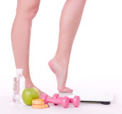 Feet with apple, dumbbells, measure and water Royalty Free Stock Images