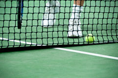 Feet approaching a ball on the tennis court. A pair of feet approaches a tennis ball behind the net of an indoor court Stock Image