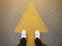 Feet and arrows on road.Feet and arrows on road. Sneakers with arrow on road background .hipster tone and selective focus royalty free stock photos