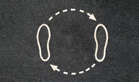 Feet and arrows. Walking is in a circle. Pair of legs standing on the road with arrows go on a circle Royalty Free Stock Photos
