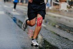 Feet athlete man in kinesiotape knee. Running wet road Stock Photography