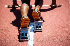 Feet of an athlete on a starting block about to run. Close-up of feet of an athlete on a starting block about to run Royalty Free Stock Photo