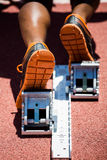 Feet of an athlete on a starting block about to run. Close-up of feet of an athlete on a starting block about to run Royalty Free Stock Photography