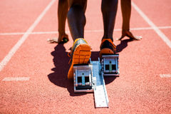 Feet of an athlete on a starting block about to run. Close-up of feet of an athlete on a starting block about to run Stock Photo