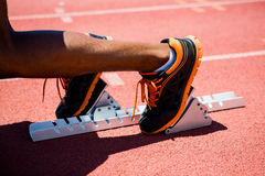 Feet of an athlete on a starting block about to run. Close-up of feet of an athlete on a starting block about to run Stock Photography