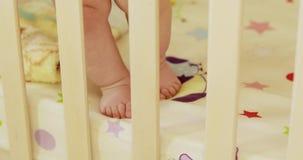 Feet Baby Boy in Crib. Baby boy legs in a wooden crib stock video footage