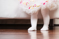 Feet of baby girl in dress. First step of baby. Part body little girl in princess fairy ballerina dress and white tights walking standing at home Royalty Free Stock Images