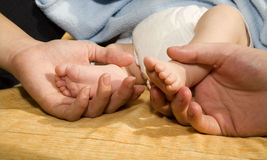 Feet of baby and the hands of parents Stock Image