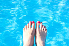 Feet on background of pool water Stock Images
